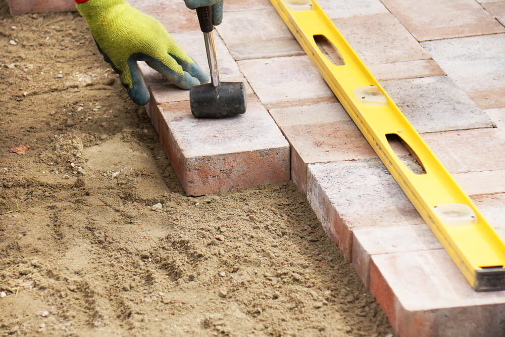 close up of a handyman gardener laying some bricks with a level laying on the bricks