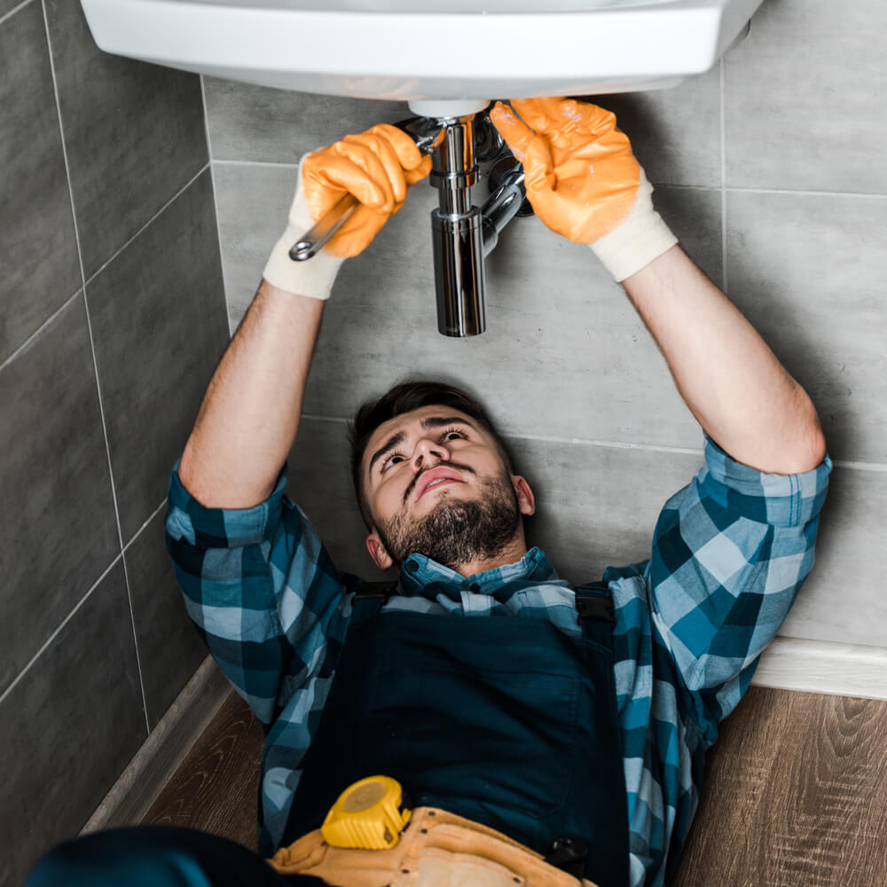image of handyman fixing a leaking sink